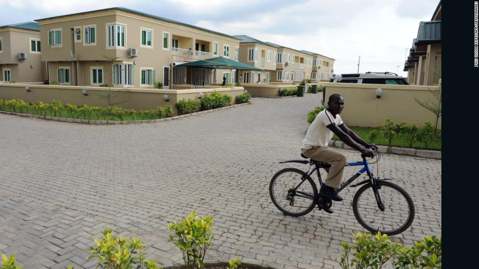 A cyclist rides past dozens of detached three-bedroom apartments in Ogun State, Nigeria on August 30.