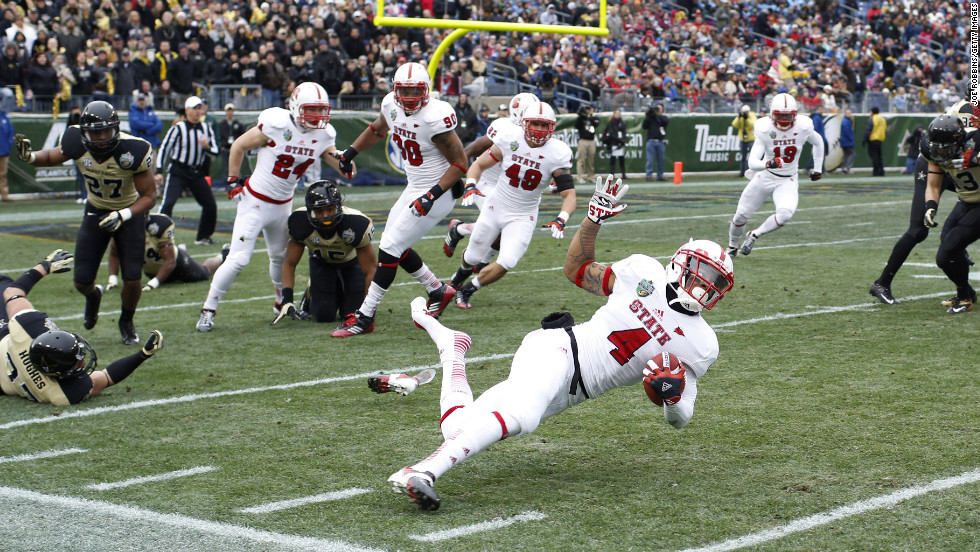 Tobais Palmer of the North Carolina State Wolfpack gets tripped up on a kick return against the Vanderbilt Commodores during the Franklin American Mortgage Music City Bowl at LP Field on December 31, in Nashville, Tennessee.