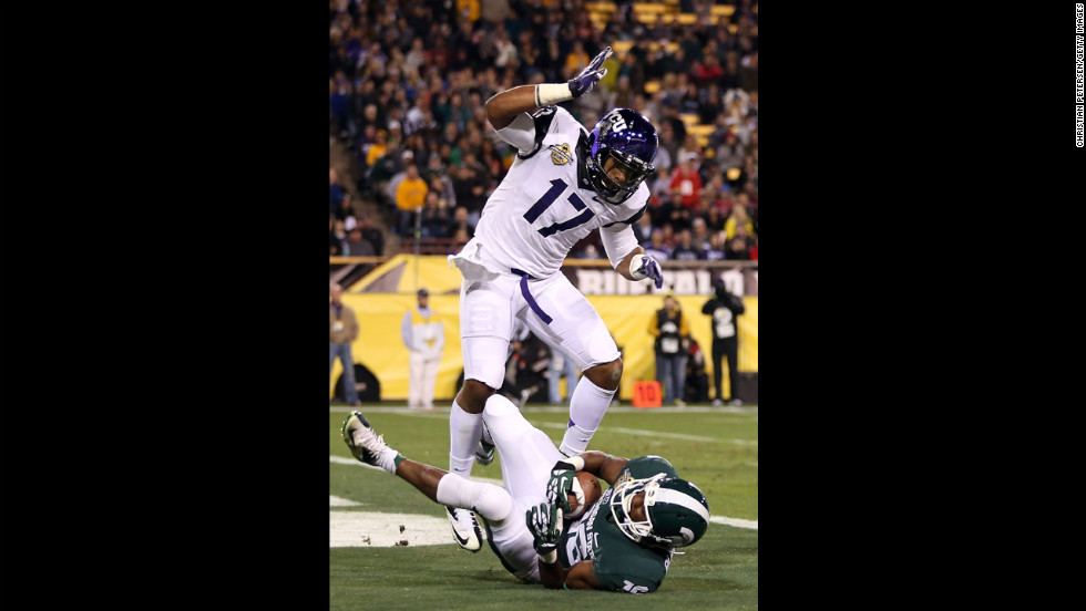 Michigan State's Aaron Burbridge scores a 15-yard touchdown past TCU's Sam Carter during the third quarter of the Buffalo Wild Wings Bowl.