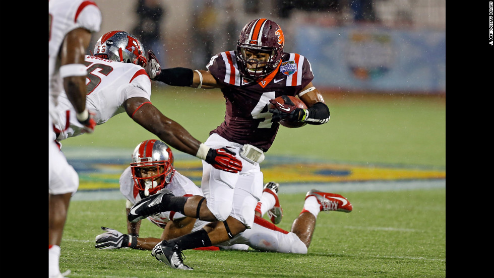 The Hokies' J.C. Coleman straight-arms Rutgers' Marvin Booker on December 28.