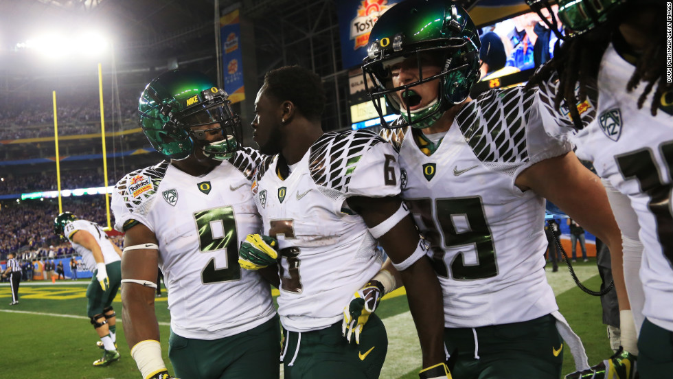 De'Anthony Thomas of the Oregon Ducks celebrates with Byron Marshall, left, and Will Murphy, right, after he returned the opening kickoff for a touchdown against the Kansas State Wildcats on January 3.