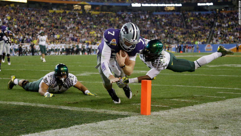 Collin Klein of the Kansas State Wildcats scores a second quarter touchdown as Ifo Ekpre-Olomu of the Oregon Ducks tries to stop him during the Tostitos Fiesta Bowl at University of Phoenix Stadium on Thursday, January 3, in Glendale, Arizona.