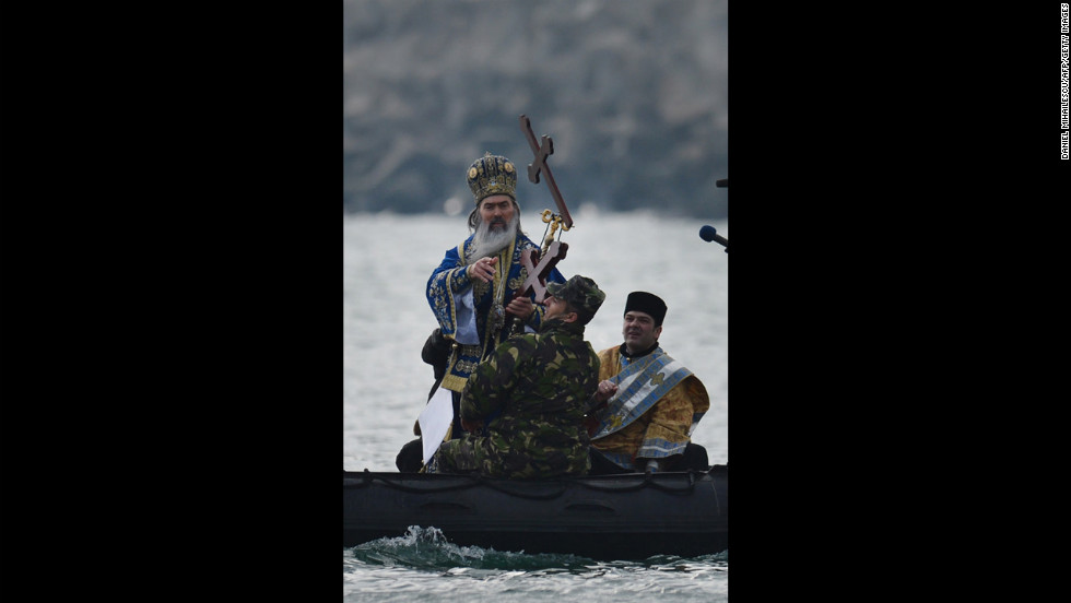 A priest throws a wooden cross in the Black Sea during a service in Constanta City, Romania, on Sunday.