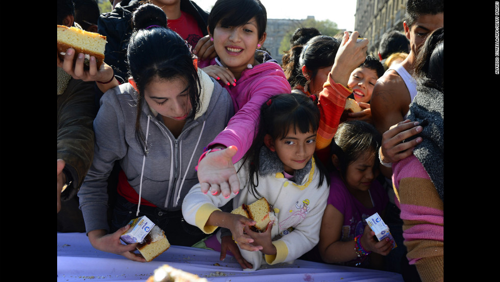 People gather to get a piece of the bread on Thursday in Mexico City.