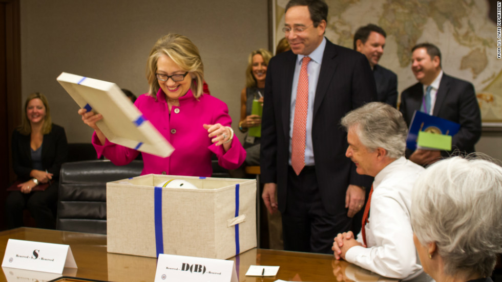 Secretary of State Hillary Clinton opens a gift from senior managers at the State Department upon returning to work on Monday.  She returned to work after being hospitalized for the flu, a concussion, and blood clot.
