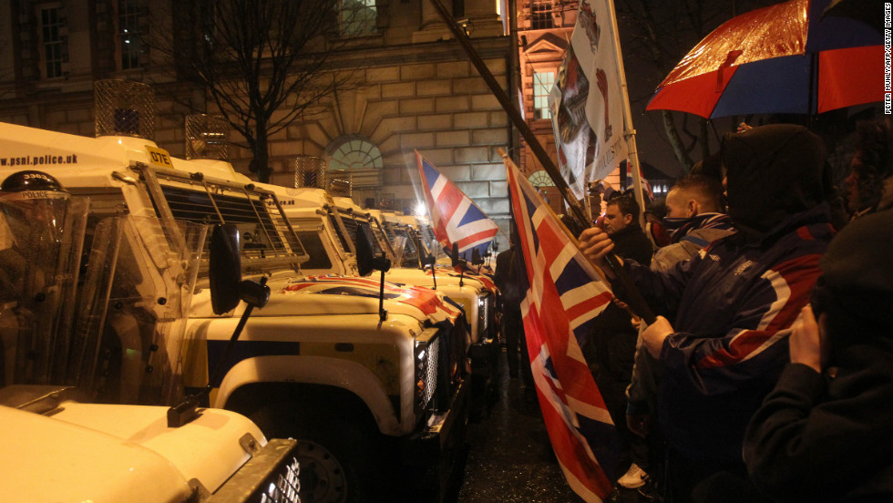 Loyalist protesters confront police as they gather at Belfast City Hall during a City Council meeting in Belfast, Northern Ireland, on Monday, January 7. Violence flared for the fifth consecutive night in Northern Ireland as pro-British demonstrators protested the council's decision to limit the number of days the British Union Jack flag can be flown above the City Hall.