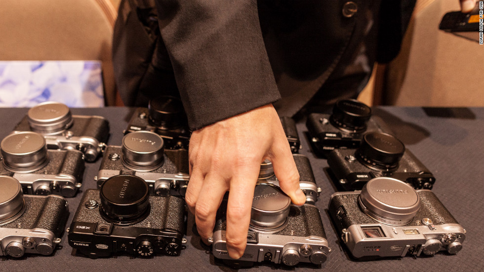 Members of the press take a peek at Fujifilm's new high-end compact cameras, the X100S and X20, on Monday.