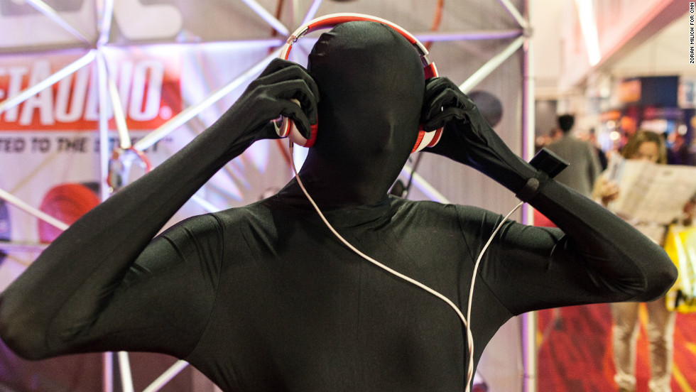 A man dressed in a full body suit wears headphones by MTX Audio.