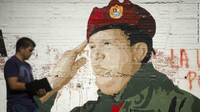 A man walks by a painting on a wall of Venezuelan President Hugo Chavez in Caracas on January 9.