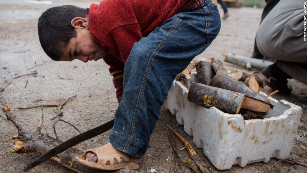 A Syrian boy cuts wood at a refugee camp near the northern city of Azaz on the Syria-Turkey border, on January 8.