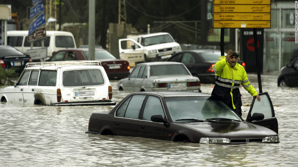 A man shouts as vehicles drive through flood waters in the southern Lebanese city of Sidon, on January 7.