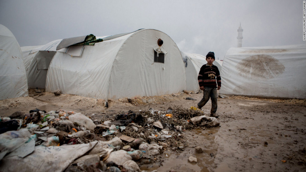 A Syrian boy walks near rubbish next to tents at a refugee camp near the northern city of Azaz on the Syria-Turkey border, home to more than 7,000 people mostly from the northern districts of Aleppo and Marea, on Tuesday, January 8.