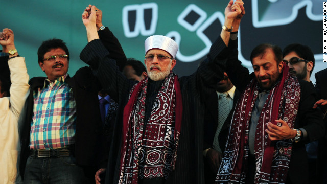 Pakistani Muslim scholar Tahir ul Qadri joins hands during a public rally in Karachi on January 1, 2013.
