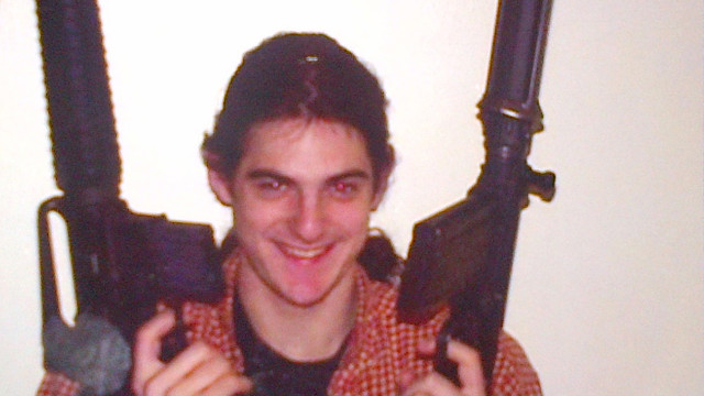 A photo shows suspect Aaron Greene posing with two guns.