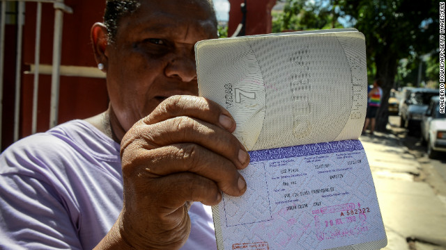 Cuban Cruz Duran shows her passport with a travel permission --aka white card-- on October 16, 2012 in Havana.