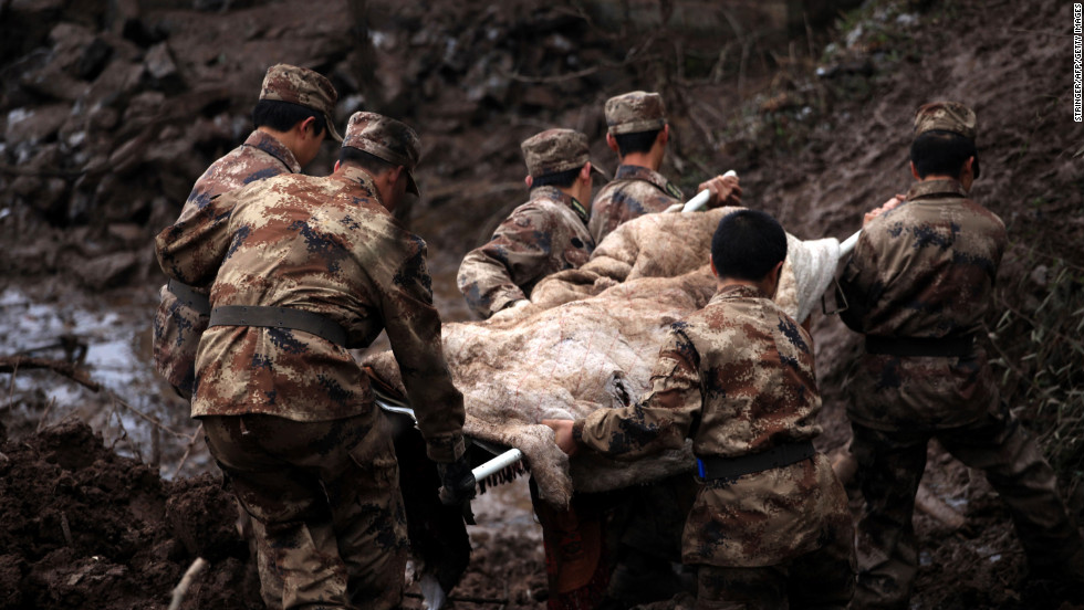 Another victim is carried away from the scene. The landslide has killed at least 46 people in the southwest China village, according to the state-run Xinhua news agency.