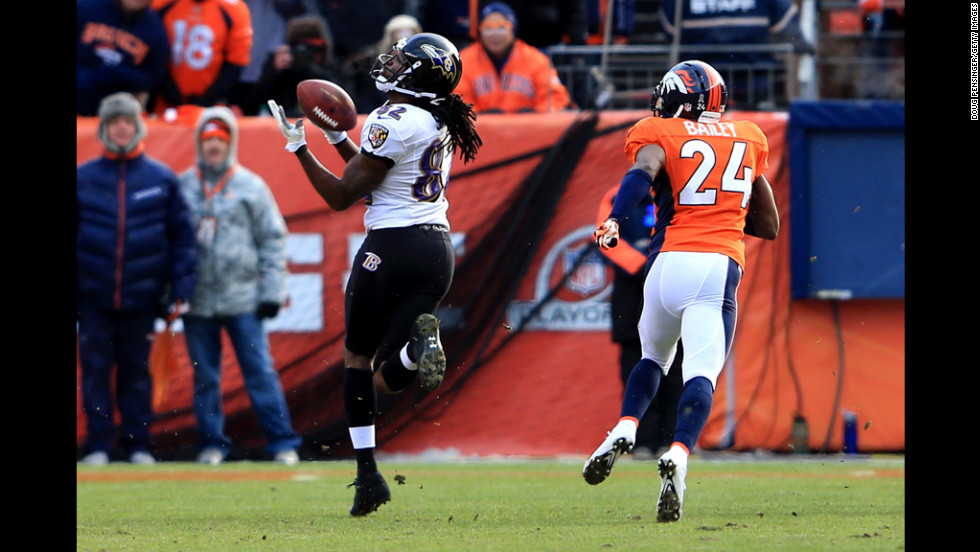Torrey Smith of the Ravens catches a pass for a 59-yard touchdown in the first quarter against Champ Bailey of the Broncos on Saturday.