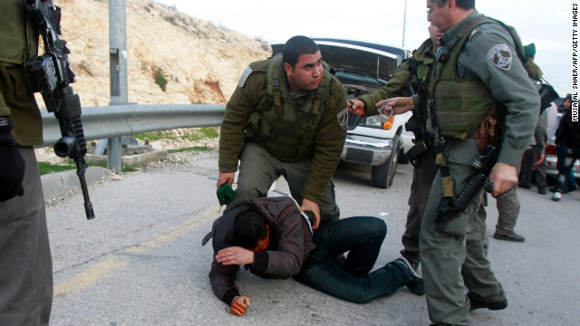 Israeli border policemen confront a Palestinian man on his way to join a protest camp on January 12.