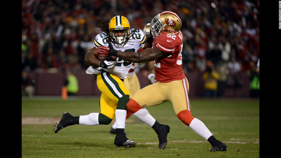 Running back DuJuan Harris of the Packers runs the ball inside linebacker Patrick Willis of the 49ers on Saturday.