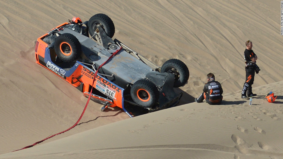 Robby Gordon of the United States, center, sits in the sand by his overturned Hummer on January 8.
