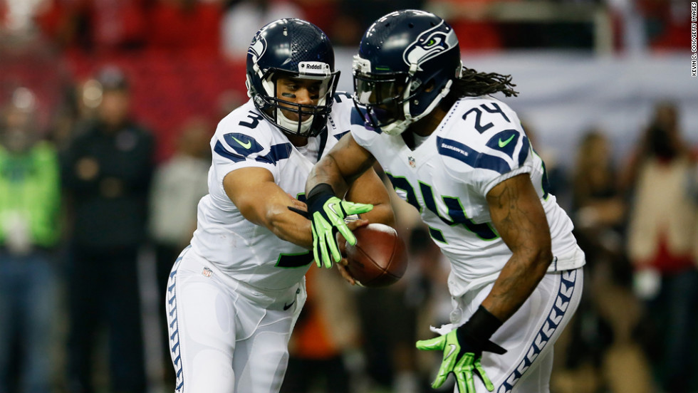 Russell Wilson hands the ball off to Marshawn Lynch of the Seahawks in the second quarter against the Falcons on Sunday.