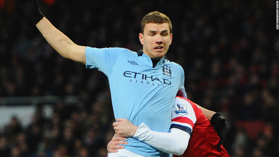 Second-placed Manchester City won 2-0 at Arsenal, who had defender Laurent Koscielny sent off in the ninth minute for this rugby tackle on Edin Dzeko.