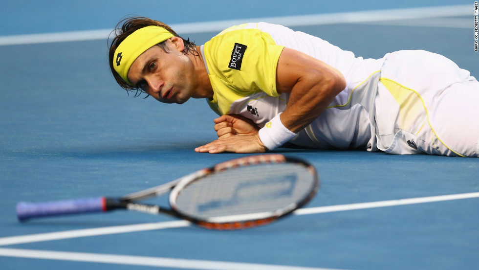 Spain's David Ferrer falls to the ground after playing a shot in his first-round match against Belgium's Olivier Rochus on January 14. Ferrer won 6-3 6-4 6-2.