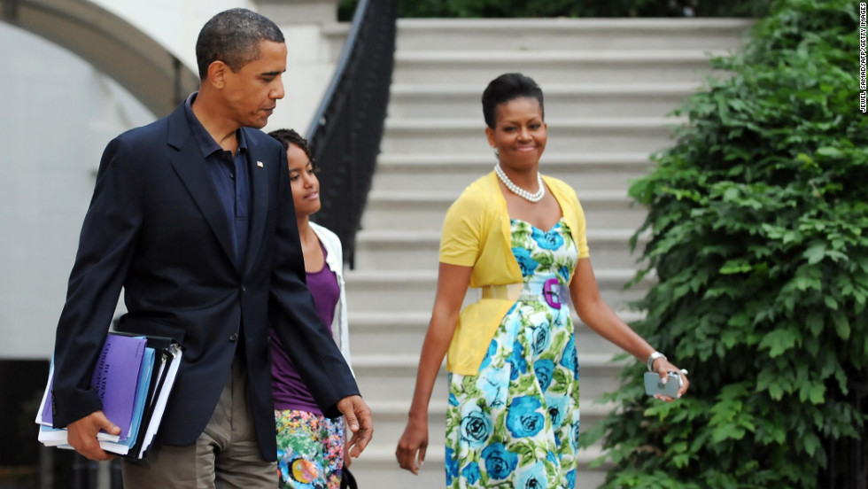 "Obama has been known to wear dresses from mass retailer Talbots and accessorize them with signature pieces such as this sweater from Dear Cashmere and a belt by Sonia Rykiel, worn in July 2009, <a href=""http://mrs-o.com/newdata/2009/7/5/bon-voyage.html"" target=""_blank"">according to Mrs. O</a>."