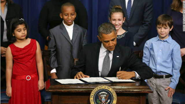 President Obama signs new gun law proposals as children who wrote letters to the White House about gun violence look on.