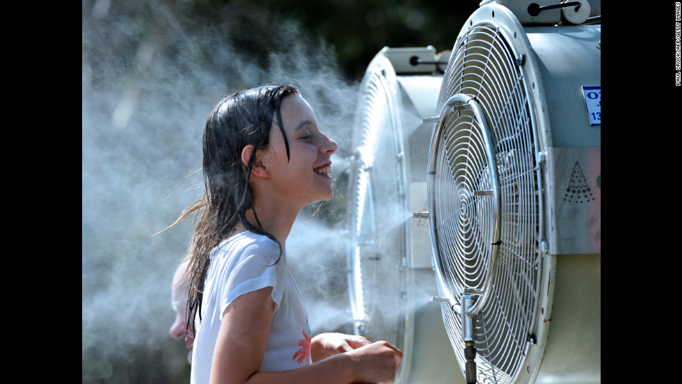 A young spectator cools off by standing in front of a water vapor machine. Temperatures reached 40 Celsius (104 Fahrenheit).
