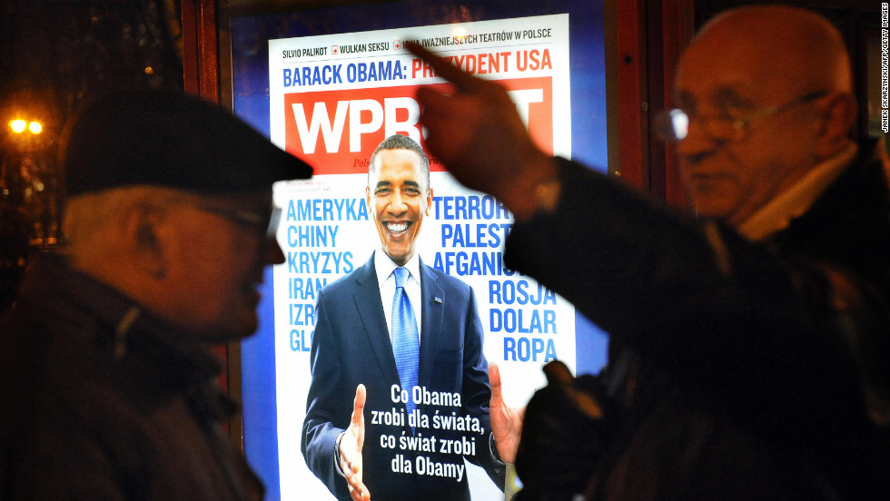 POLAND: Two men talk in front of an advertisement for a Polish weekly magazine in Warsaw on January 20, 2009.