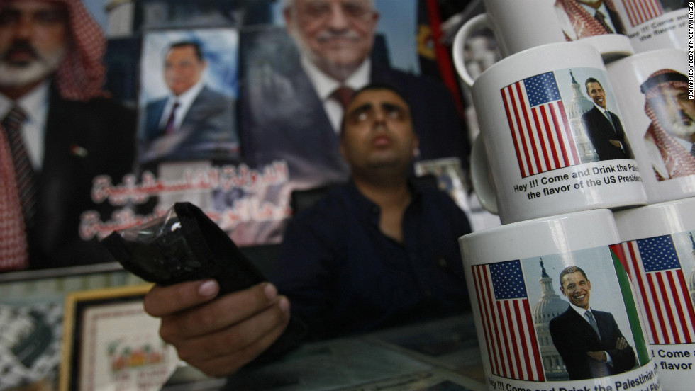 "GAZA: A Palestinian shopkeeper sits near coffee mugs for sale with pictures of Obama and Hamas leader Ismail Haniya on November 2, 2008, in Gaza City. The mugs read ""Hey!!! Come and drink the Palestinian coffee with the flavor of the US Presidential Election."""