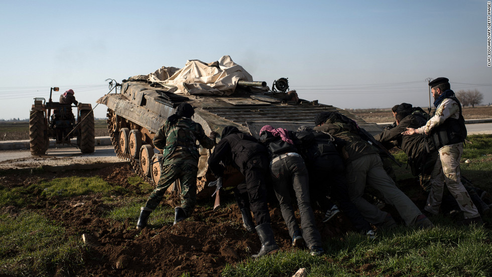 Rebel fighters push an abandoned Syrian army tank with the aid of a tractor in Aleppo on January 18. The tank is to be repaired and used by rebels.