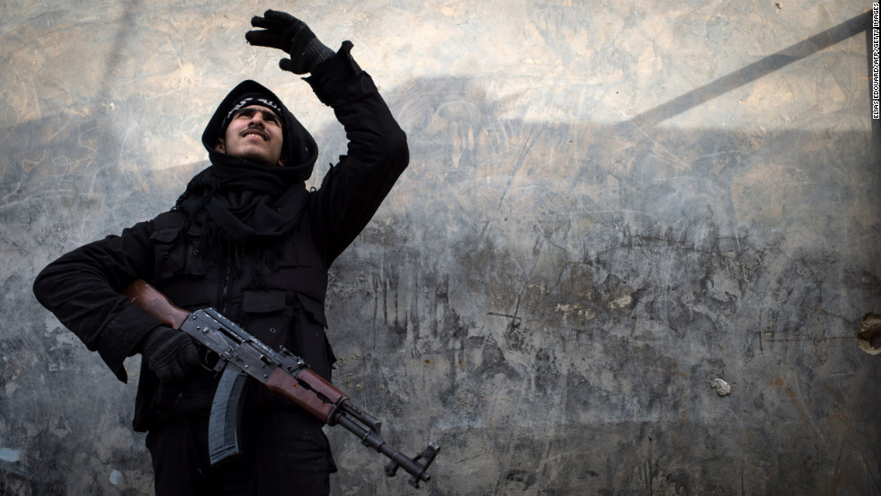 A Syrian rebel fighter tries to locate a government jet fighter in Aleppo on Friday, January 18.