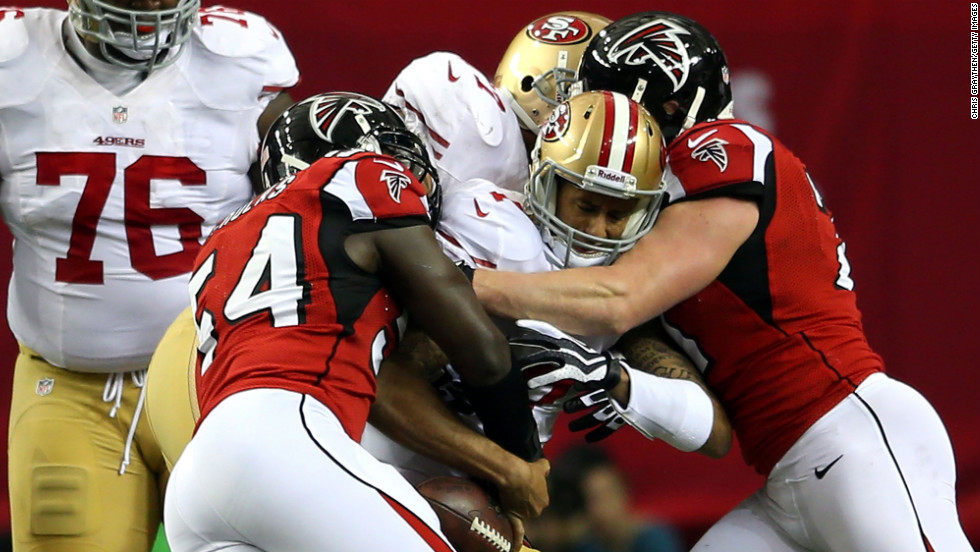Quarterback Colin Kaepernick of the San Francisco 49ers is tackled by Stephen Nicholas, left, and Kroy Biermann of the Atlanta Falcons.