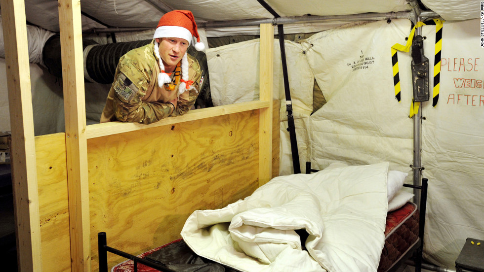 Harry shows a TV crew his sleeping area in the VHR tent while wearing a Santa hat on December 12, 2012.