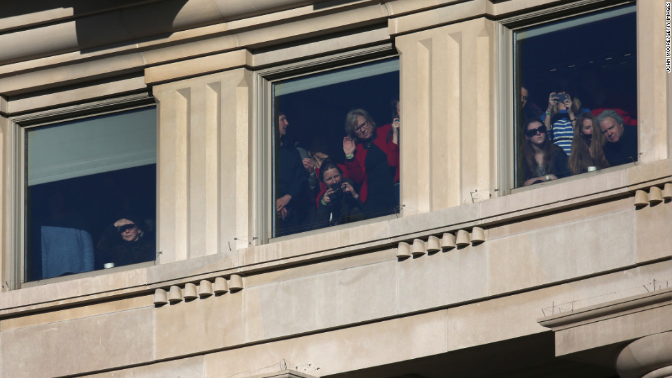 People watch as President Barack Obama and first lady Michelle Obama are driven past crowds during the Inauguration parade on Monday, in Washington. President Obama was sworn in for a second term office at the U.S. Capitol building.