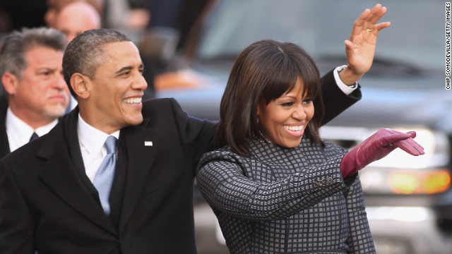 U.S. President Barack Obama and first lady Michelle Obama wave to supporters as they walk the inaugural parade route down Pennsylvania Avenue January 21, 2013 in Washington, DC. President Obama took the oath of office earlier in the day during a ceremony on the west front of the U.S. Capitol.