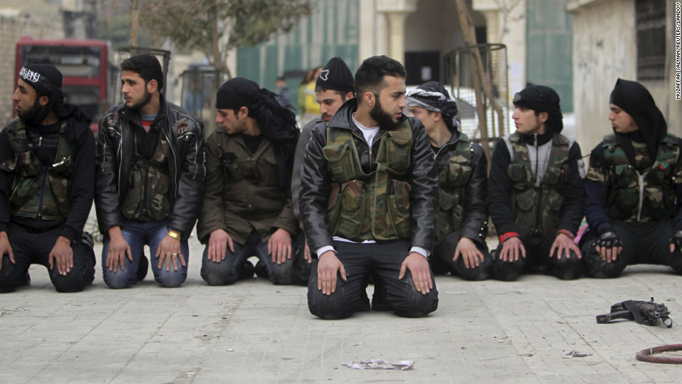 Members of the Free Syrian Army pray on one of the streets of Aleppo on January 21.