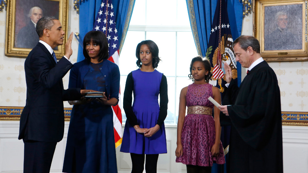 President Obama takes the oath of office from U.S. Supreme Court Chief Justice John Roberts as first lady Michelle Obama holds the bible and their daughters Malia, center, and Sasha look on in the Blue Room of the White House in Washington, on Sunday, January 20.