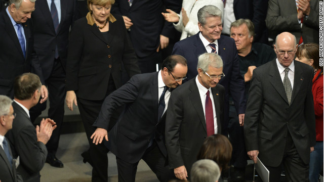 French President Francois Hollande stumbles as he arrives at the Reichstag with German Chancellor Angela Merkel.