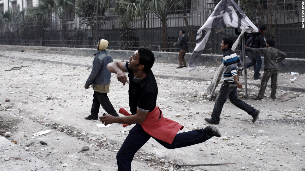 A protester throws a rock at riot police on January 26, in Cairo.