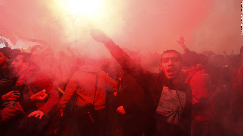 A fan of Al-Ahly football club lights a flare as club supporters celebrate on January 26 in Cairo.