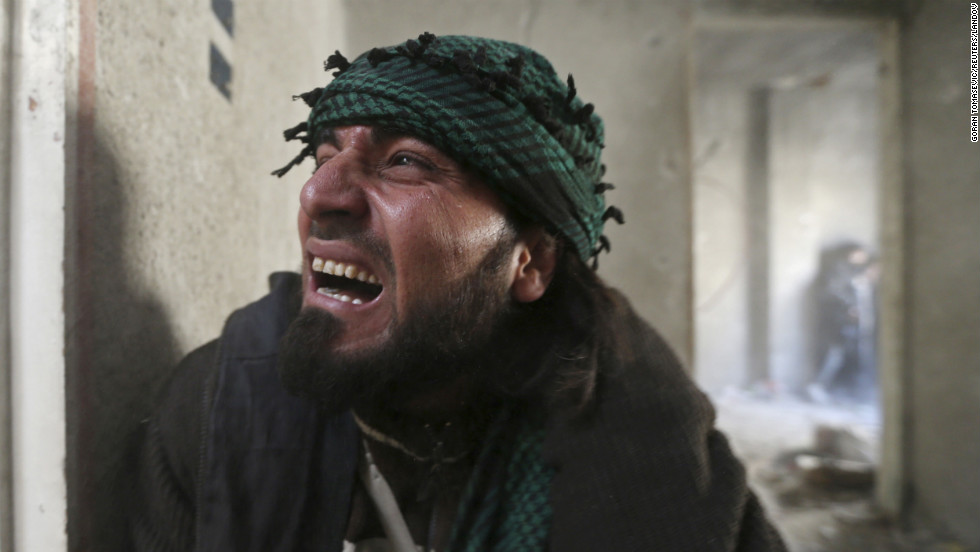 A rebel fighter screams in pain after being wounded by shrapnel from a hand grenade during heavy fighting in Damascus on January 26.