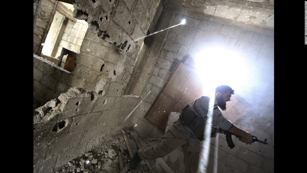 A rebel fighter fires back at Syrian army soldiers in Damascus on January 26.