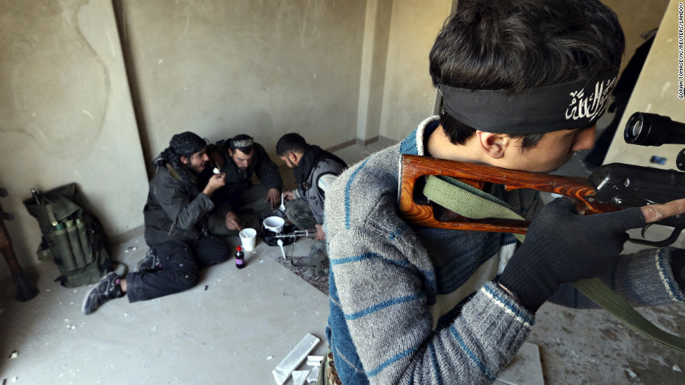 A rebel fighter aims a sniper rifle as other fighters eat their lunch during heavy fighting in Damascus on January 26.