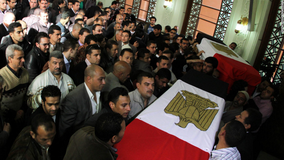 Egyptian policemen and relatives on January 27 gather upon the arrival of the coffins of their colleagues killed in the violence one day earlier in Cairo.