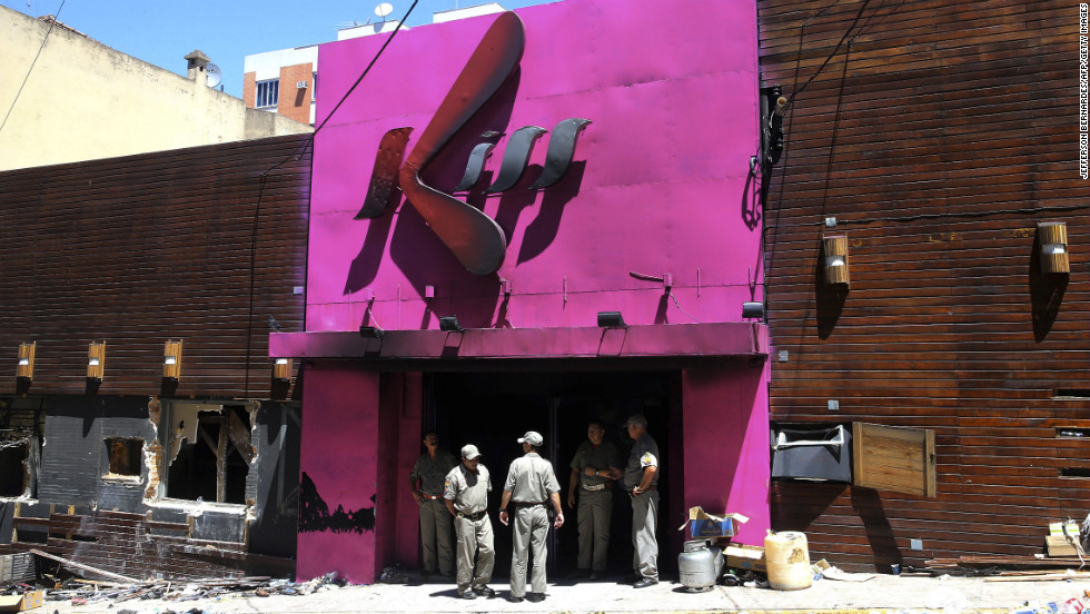 Firefighters stand at the burnt-out entrance of the Kiss nightclub on Sunday, January 27, in Santa Maria, Brazil.