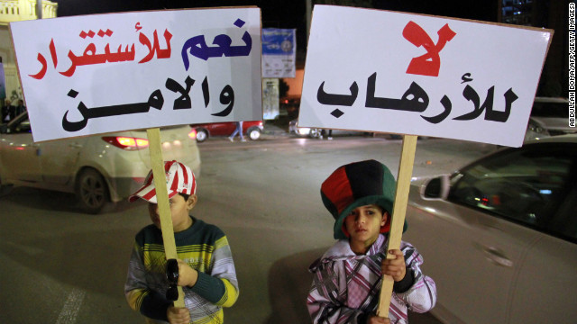 "Children in Benghazi hold up placards reading ""No to terrorism"" (R) and ""yes for stability and security"" on January 15."