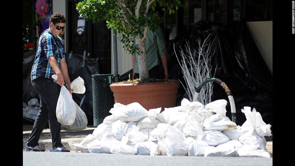A man lugs sandbags in front of shops in Brisbane's inner city suburb of Rosalie before high tide on January 29.